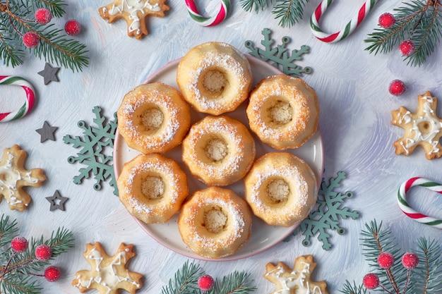 Mini-gâteaux en anneau avec du sucre glace avec des brindilles de sapin, des baies et des cannes de bonbon