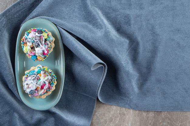 Mini gâteaux sur une assiette sur des morceaux de tissu sur du marbre.