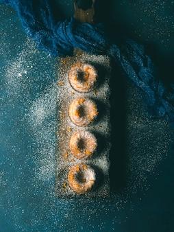 Mini-gâteaux en forme d'anneau avec du sucre glace au zeste d'orange sur un plateau de service bleu foncé. vue de dessus. noël sucré tonique