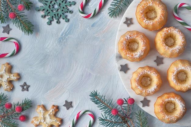 Mini-gâteaux en forme d'anneau avec du sucre glace sur de la lumière avec des brindilles de sapin, des baies et des cannes de bonbon
