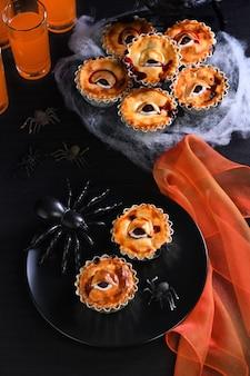 Mini gâteaux pour les yeux effrayants d'halloween avec garniture aux cerises
