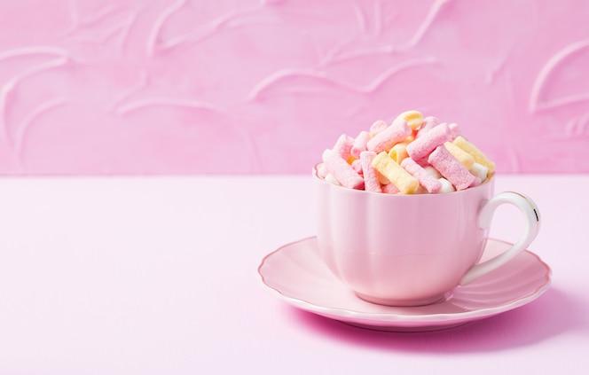 Mini guimauve colorée dans une tasse rose