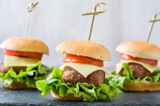 Mini hamburgers au fromage avec des légumes sur une table en bois