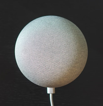 Mini haut-parleur intelligent à commande vocale grise sur fond noir