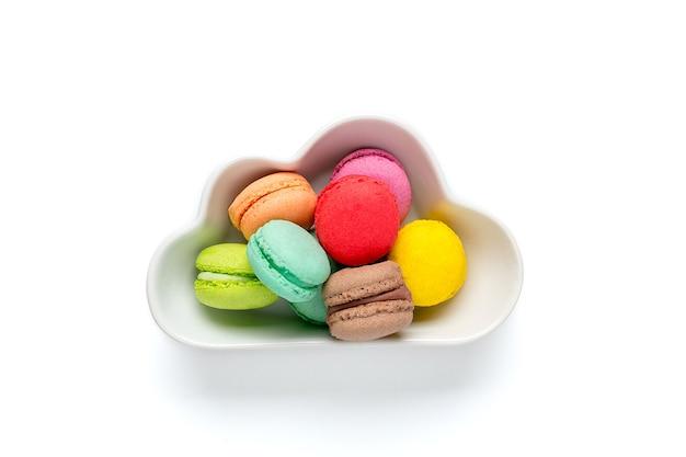 Mini macaron coloré dans un bol en forme de nuage isolé