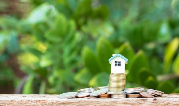Mini maison sur pile de pièces de monnaie sur la nature floue