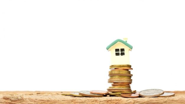 Mini maison sur pile de pièces.