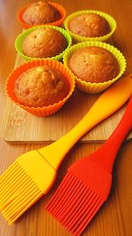 Mini muffins simples dans des ustensiles de cuisson en silicone colorés. cupcakes en silicone et pinceaux en silicone. concept de cuisine et de cuisson sur fond de bois