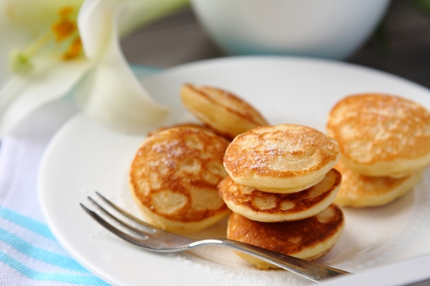 Mini pancakes hollandais appelés poffertjes, saupoudrés de sucre en poudre
