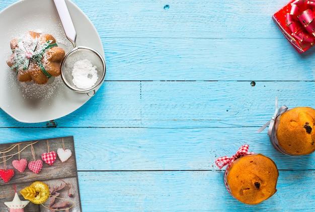 Mini panettone aux fruits et décoration de noël sur fond en bois bleu