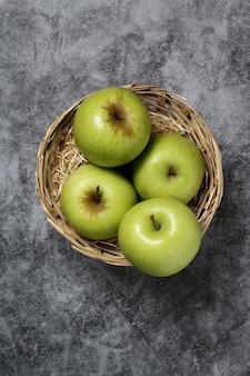 Mini panier avec quatre pommes vertes