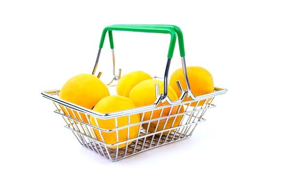 Mini panier de supermarché avec des abricots mûrs isolés sur fond blanc.