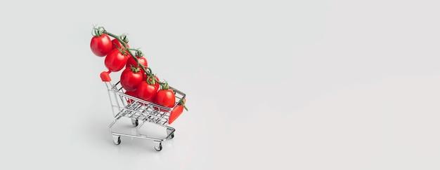 Mini panier avec des tomates cerises sur gris clair