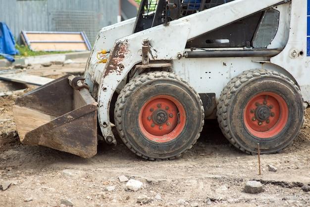 La mini-pelle sur un chantier de construction charge le sol avec un godet avant, en gros plan