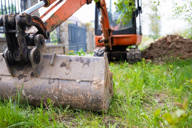 Mini pelle de couleur orange. location de matériel de chantier.
