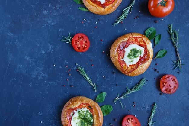 Mini pizza maison avec tomates, fromage et bacon, blessures et épices.