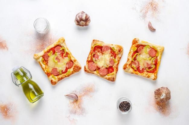 Mini pizzas de pâte feuilletée avec saucisses.