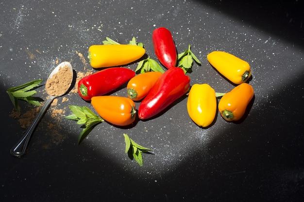 Mini poivrons colorés sur fond noir ensoleillé. vue de dessus de poivrons jaunes, rouges et oranges.