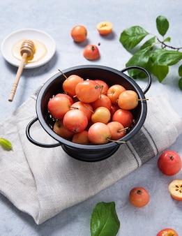 Les mini pommes juteuses se trouvent dans un bol sur une serviette en lin.