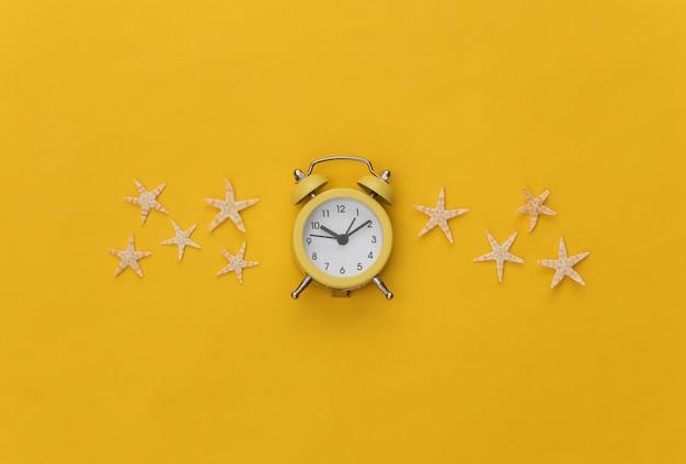 Mini Réveil Et étoile De Mer Sur Fond Jaune. Temps De Vacances D'été. Photo Premium