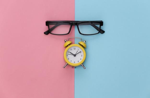 Mini réveil et lunettes sur fond bleu rose.