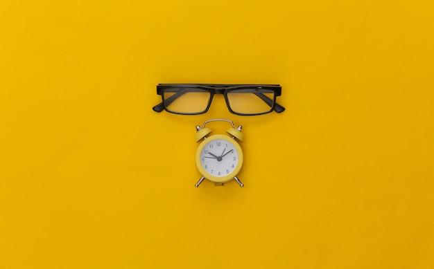 Mini réveil et lunettes sur fond jaune.