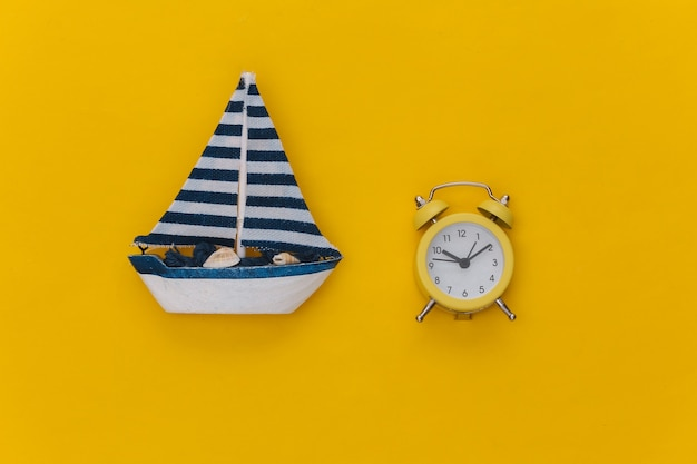 Mini réveil et mini voilier sur fond jaune. le temps de voyager.