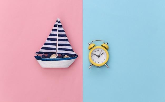 Mini réveil et mini voilier sur fond pastel bleu rose. le temps de voyager.