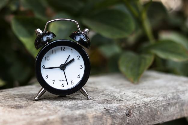 Mini réveil noir sur une surface en bois dans la nature, feuillage vert sur fond. notion de temps. image abstraite.