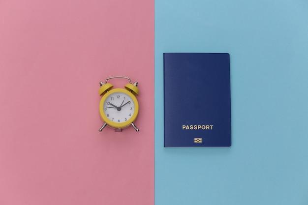 Mini réveil et passeport sur fond pastel bleu rose. le temps de voyager.
