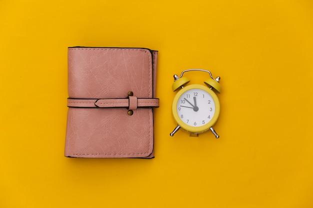 Mini réveil et portefeuille sur fond jaune.