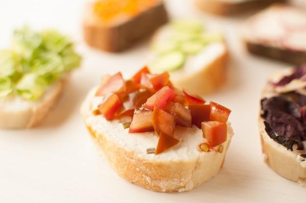 Mini sandwich à la baguette française et à la tomate sur une plaque blanche vue de dessus