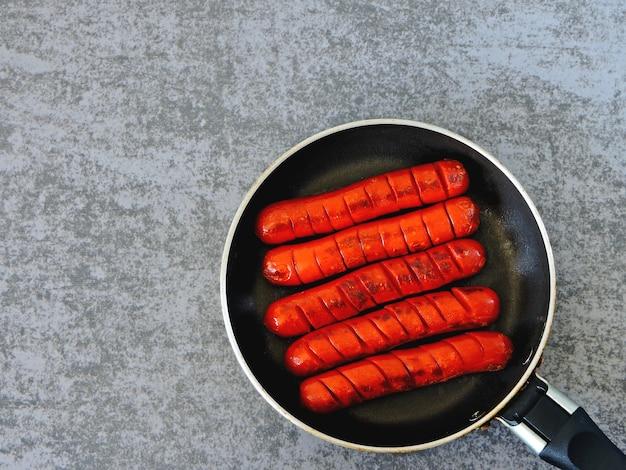 Mini saucisses chaudes juteuses dans une petite poêle.