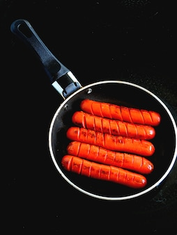 Mini saucisses dans une poêle, croûtons, fromage et légumes.