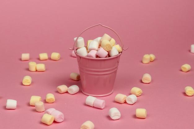 Mini seau avec beaucoup de guimauves sur fond rose pastel. minimalisme. bonbons