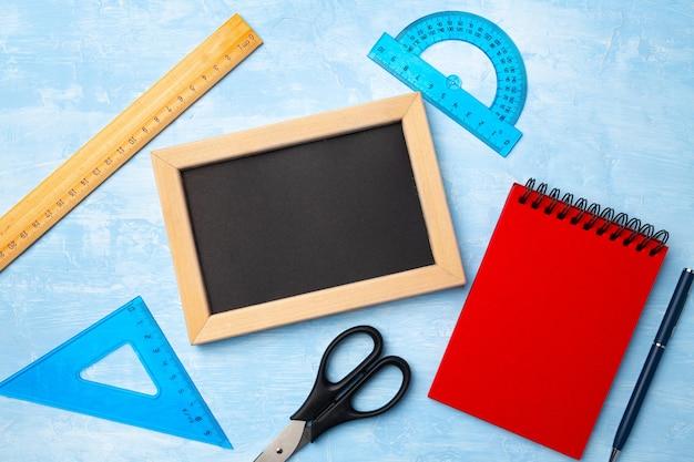 Mini tableau noir dans un cadre en bois et des fournitures scolaires vue de dessus