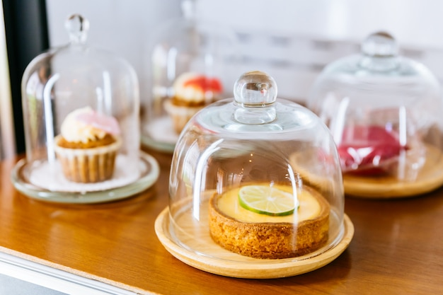 Mini-tarte au citron vert recouverte d'une tranche de citron vert dans une assiette en bois et recouverte d'une cloche de verre.