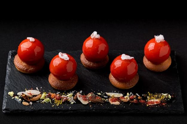 Mini tartelettes de baies glacées sur le dessus joliment disposées sur une plaque noire. mousse à tartelette festive pour dessert moderne et glaçage miroir rouge en forme de chapeau de père noël.