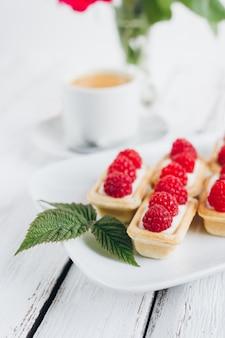 Mini tartelettes avec du fromage cottage et des framboises fraîches et une tasse de café