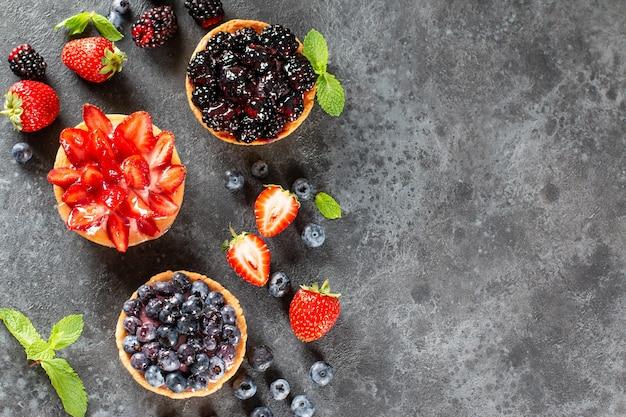 Mini tartelettes fraîchement préparées avec des baies sur une table. cuisson des fruits d'été. espace de copie. vue de dessus.