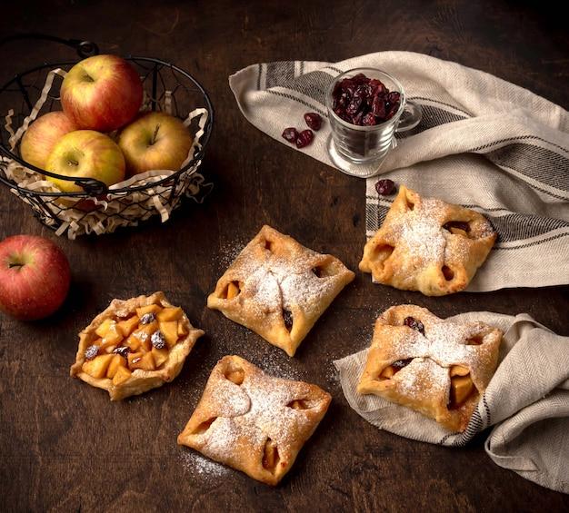 Mini tartes aux pommes savoureuses avec du sucre en poudre sur un fond rustique foncé