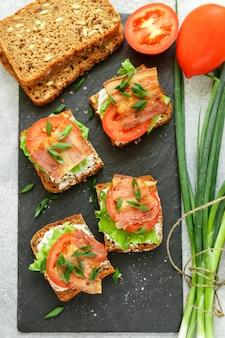 Mini toast de pain aux céréales avec tomates, bacon, laitue et oignons verts