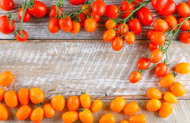 Mini tomates colorées sur table en bois, pose à plat.