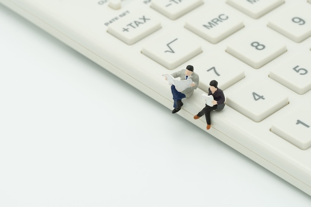 Miniature 2 personnes assises sur une calculatrice blanche