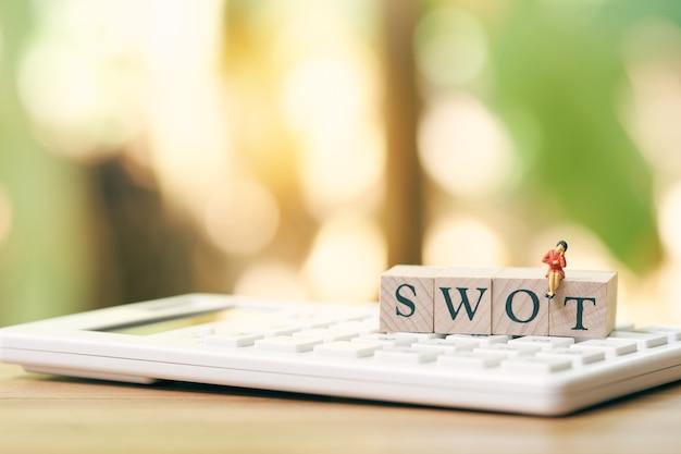 Miniature 4 personnes assis sur un mot bois swot placé sur une calculatrice blanche