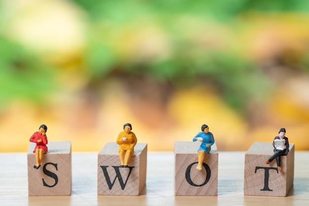 Miniature 4 personnes assises sur le mot bois swot