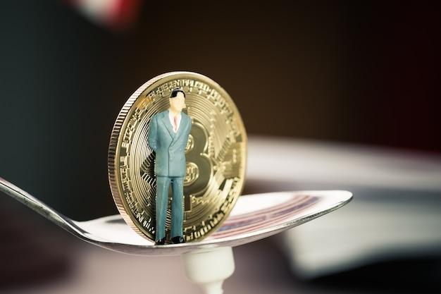 Miniature affaires debout sur cuillère près de bitcoin digital argent virtuel.