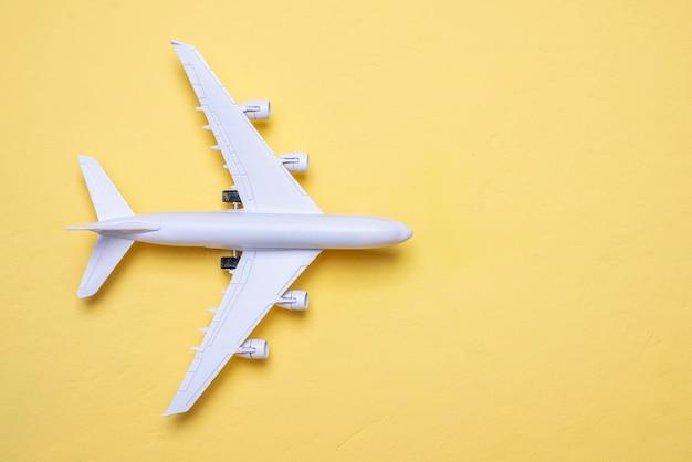 Miniature d'un avion sur fond jaune avec un espace de copie, vue du dessus