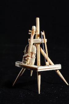 Miniature en bois de violon sur fond noir. violon debout sur un support en bois.
