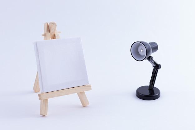 Miniature de chevalet en bois avec toile carrée blanche vierge et lampe de table